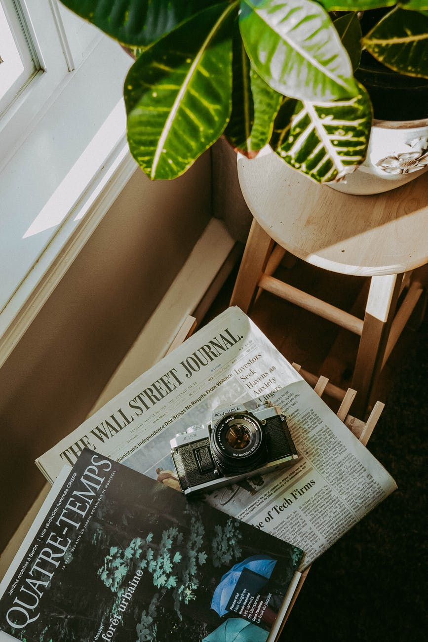 black and silver camera on newspaper